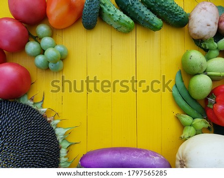 Autumn vegetables on a yellow background. Zucchini, eggplant, tomatoes, cucumbers, green peas, sunflowers, peppers, nuts and potatoes-background. Harvest.