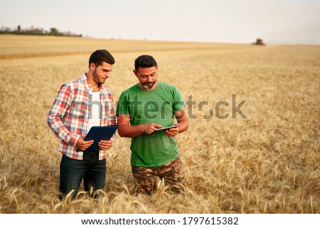 Two farmers stand in wheat stubble field, discuss harvest, crops. Senior agronomist with touch tablet pc teaches young coworker. Innovative tech. Precision farming with online data management soft. #1797615382