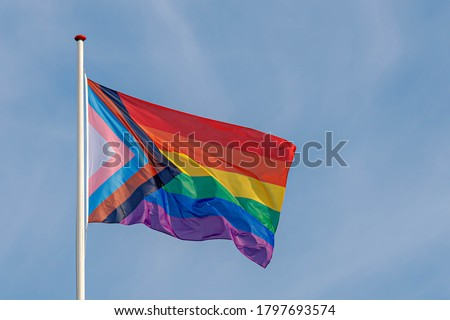 Progress pride flag (new design of rainbow flag) waving in the air with blue clear sky, Celebration of gay pride, The symbol of lesbian, gay, bisexual and transgender, LGBTQ community in Netherlands. Royalty-Free Stock Photo #1797693574