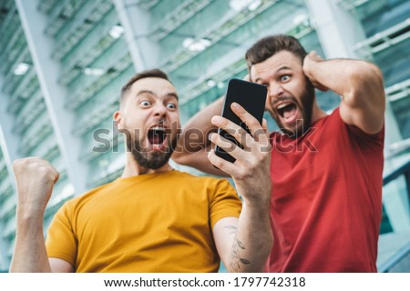 Two friends showing sincere emotions of joy about victory in online lottery. Men being happy winning a bet in online sport gambling application with football stadium on the background. Royalty-Free Stock Photo #1797742318