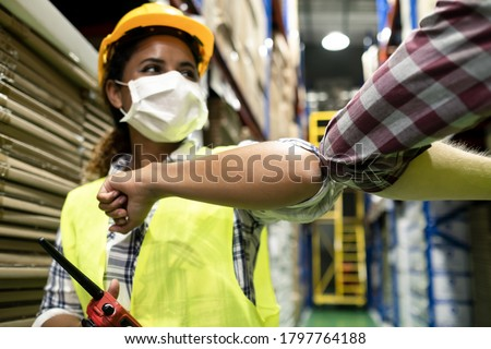 Two colleague female and male workers in warehouse factory have a greeting by touching the elbow or elbow bump to prevent the COVID infection. All people wear mask in industrial workplace for health. Royalty-Free Stock Photo #1797764188