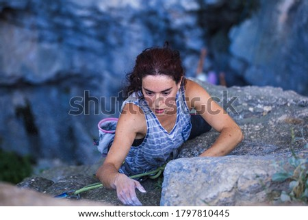 A woman is climbing in Turkey, Turkish woman climbs the rock, Extreme hobby, Overcoming a difficult climbing route, Overcoming the fear of heights, Climbing effort. #1797810445