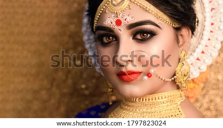 Beautiful bride with wedding makeup and jewelry .Indian Bridal fashion model with open eyes posing in interior. Royalty-Free Stock Photo #1797823024