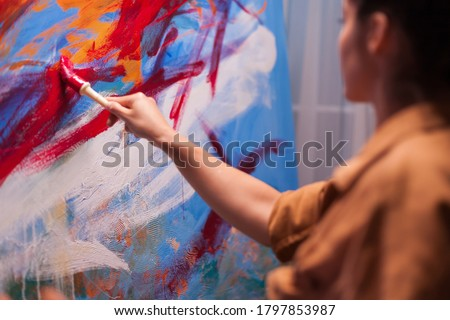 Woman artist holding paint brush on large canvas in art studio. Modern artwork paint on canvas, creative, contemporary and successful fine art artist drawing masterpiece Royalty-Free Stock Photo #1797853987
