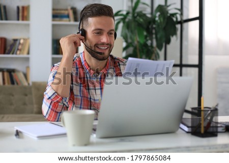 Concentrated freelancer businessman using laptop for video conferance, working remotely online at home. Smiling friendly handsome young male call center operator manager Royalty-Free Stock Photo #1797865084