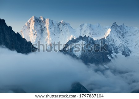 Grandes Jorasses and Mer de Glace behind the clouds. Winter season in France. First snow in Chamonix valley in Haute Savoie. Popular climbing attraction. Europe Alps summits  Royalty-Free Stock Photo #1797887104