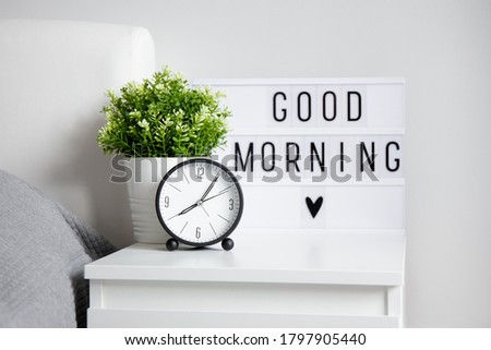 "good morning concept - alarm clock, houseplant and lightbox with ""good morning"" words on bedside table in bedroom"