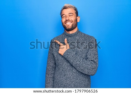 Young handsome blond man wearing casual sweater standing over isolated blue background smiling cheerful pointing with hand and finger up to the side