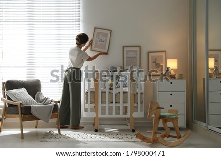 Decorator hanging picture on wall in baby room. Interior design Royalty-Free Stock Photo #1798000471