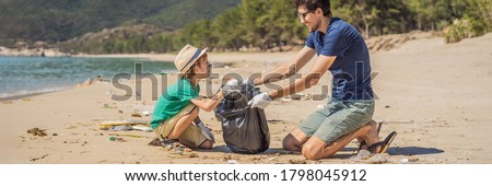 Dad and son in gloves cleaning up the beach pick up plastic bags that pollute sea. Natural education of children. Problem of spilled rubbish trash garbage on the beach sand caused by man-made Royalty-Free Stock Photo #1798045912