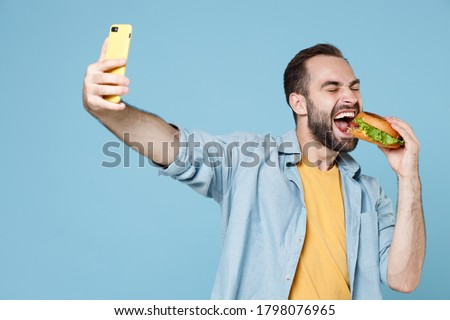 Crazy young bearded man 20s in casual clothes posing hold biting american classic fast food burger doing selfie shot on mobile phone isolated on pastel blue background studio portrait