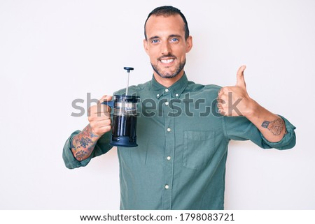 Young handsome man with tattoo holding french coffee maker smiling happy and positive, thumb up doing excellent and approval sign