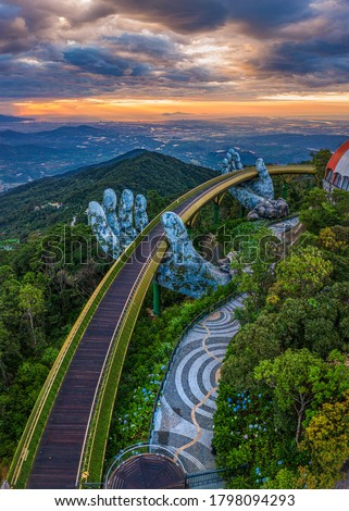 Aerial view of the Golden Bridge is lifted by two giant hands in the tourist resort on Ba Na Hill in Da Nang, Vietnam. Ba Na mountain resort is a favorite destination for tourists #1798094293