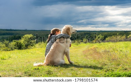 Back view of beautiful little girl hugging loyal dog in nature Royalty-Free Stock Photo #1798101574