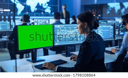 Confident Female Data Scientist Works on Personal Computer with Green Screen Mock Up in Big Infrastructure Control and Monitoring Room. Woman Engineer Uses Computer in an Office Room with Colleagues.