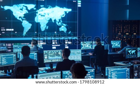 Team of Professional Computer Data Science Engineers Work on Desktops with Screens Showing Charts, Graphs, Infographics, Technical Neural Network Data and Statistics. Dark Control and Monitoring Room. Royalty-Free Stock Photo #1798108912