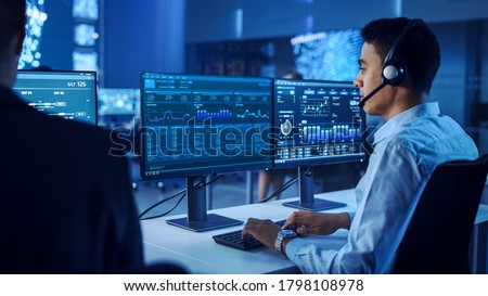 Confident Male Data Scientist Works on Personal Computer Wearing a Headset in Big Infrastructure Control and Monitoring Room. Young Engineer in a Business Call Center Office Room with Colleagues. Royalty-Free Stock Photo #1798108978