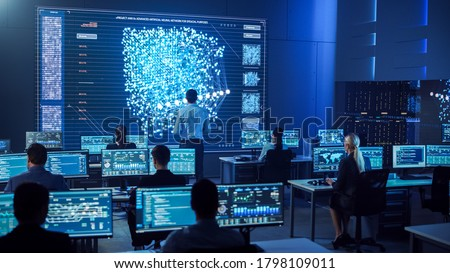 Team of Professional Computer Data Science Engineers Work on Desktops with Screens Showing Charts, Graphs, Infographics, Technical Neural Network Data and Statistics. Dark Control and Monitoring Room. Royalty-Free Stock Photo #1798109011