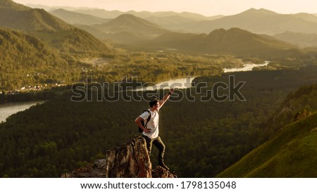 Hiker with a backpack at sunset on the top of a mountain enjoying the sunset with a raised hand in a winner's pose against the background of the river. Travel and vacation concept. hiker in the mounta #1798135048
