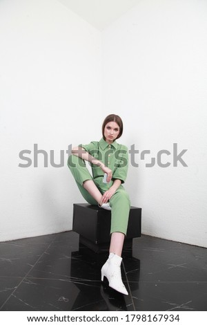 Front portrait of woman with slicked down hair, wearing cotton summer light green suit. The girl is sitting on the black cube and looking to camera on white background,