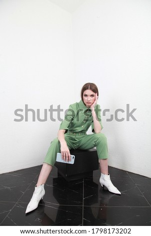 A young European lady with slicked back brown hair is posing on the white backdrop. The girl in a cotton green suit is resting with her hand on the knee.