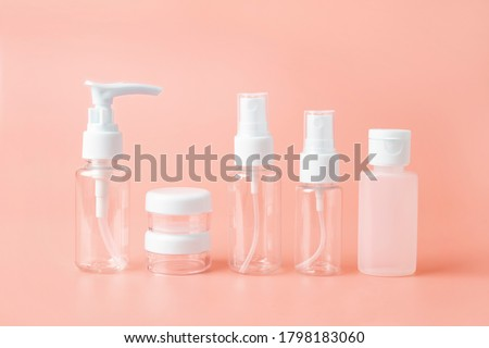 Set of empty travel women toiletries beauty kit on beige orange background. Approved for airplane luggage bottle container size. Isolated with copy space for text for beauty social media Royalty-Free Stock Photo #1798183060