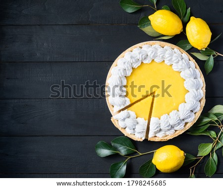 Homemade lemon pie with meringue, cutted piece, with fresh lemons on black wooden background, top view, copyspace.