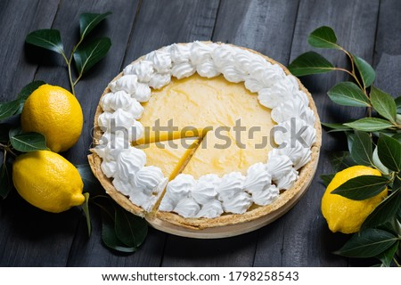 Homemade lemon pie with meringue, cutted piece, with fresh lemons on black wooden background, selective focus, horizontal orientation.