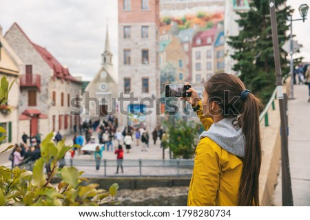 Quebec city old town woman tourist taking picture with phone of famous wall art mural in Place Royale, Autumn Canada travel.