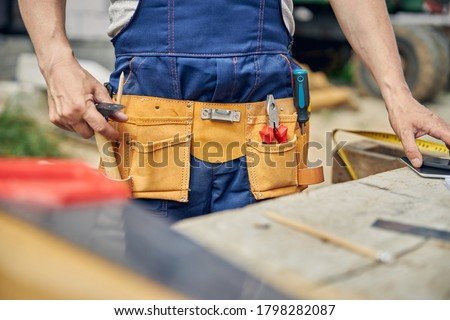 Cropped photo of a builder wearing a tool belt and workwear at the construction site