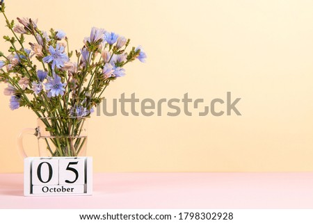Flowers in a glass cup and calendar with date of October 5, on a colored yellow pink background, Teacher's Day concept.