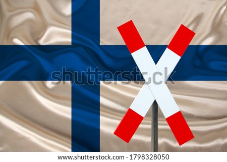 customs sign, stop, attention against the background of the silk national flag of Finland, the concept of border and customs control, violation of the state border, tourism restrictions