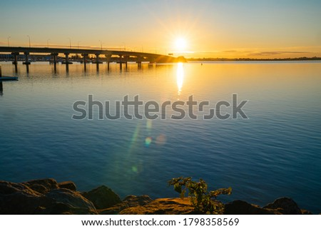 Sweeping lines of Tauranga Harbour Bridge over calm blue water with glow of rising sun at far end over horizon.
