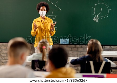 Black teacher with protective face mask teaching her students on a class at elementary school. Royalty-Free Stock Photo #1798363267