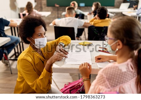 African American teacher and schoolgirl wearing protective face masks while discussing about test results on a class at the school.  #1798363273