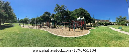 Panorama view urban playground at public park surrounded by large trees and skylines background in downtown Dallas, Texas, USA. Empty recreation place in hot summer day with sunny clear blue sky Royalty-Free Stock Photo #1798455184