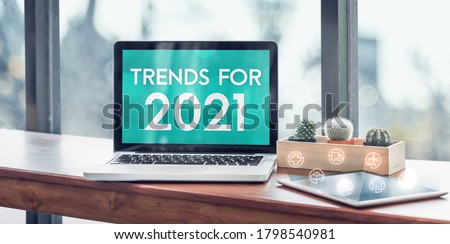Trends for 2021 in laptop computer screen with icon floating on tablet on wood stood table in at window with blur background,Digital Business or marketing trending Royalty-Free Stock Photo #1798540981