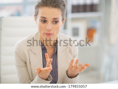 Portrait of business woman in office explaining something #179855057