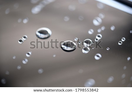 Water droplet on the car hood. Water beading after rain or car wash on black shiny paint surface. Beading created by ceramic coat or paint sealant with high surface tension. Water drop background. Royalty-Free Stock Photo #1798553842
