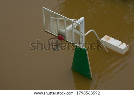 During the rainy season, heavy rain flooded the river and flooded the basketball court.