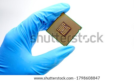 Engineer hand wearing blue rubber gloves holding chipset cpu,the concept of computer, service, electronics, hardware, repairing, upgrade and technology. #1798608847