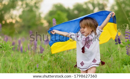 Ukraine's Independence Flag Day. Constitution day. 24 August. Patriotic holiday. Girl in traditional embroidery with flag of Ukraine. Child carries fluttering blue and yellow flag of Ukraine in field. #1798627360