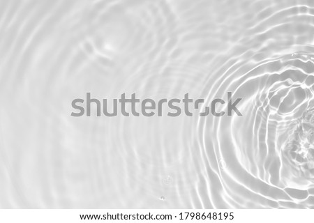 Blurred desaturated transparent clear calm water surface texture with splashes and bubbles. Trendy abstract nature background. White-grey water waves in sunlight. Copy space. Royalty-Free Stock Photo #1798648195