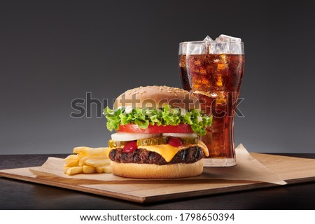 burger, fries and coke on the wood table