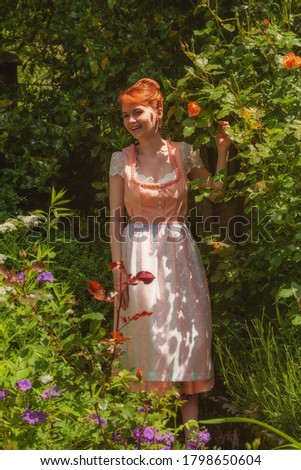 Young woman in dirndl laughing in your garden and happily holding a rose in her hand. #1798650604