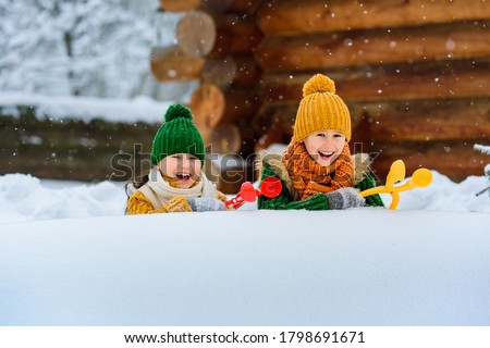 Two small smiling children have fun making snowballs with toy plastic maker. Kids playing snowballs among the snowdrifts. Winter games outdoors. Place for text.
