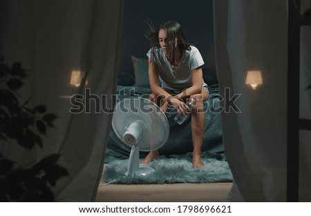 Exhausted woman suffering suring the heatwave, she is holding a water bottle and sitting in front of a cooling fan in the bedroom Royalty-Free Stock Photo #1798696621