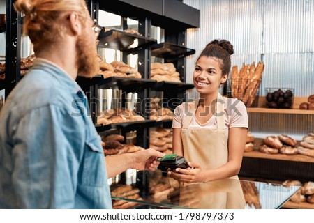 Young woman assistant wearing apron holding card machine taking payment for purchase from customer at bakery shop small business smiling friendly