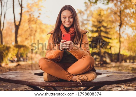 Photo of pretty charming lady smiling sit bench hold telephone send autumn picture friend social network city park wear scarf green turtleneck orange windbreaker pants outdoors
