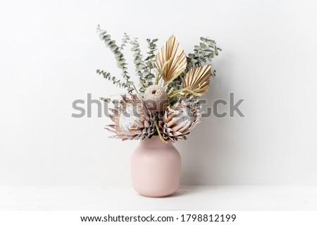 Beautiful dried flower arrangement in a stylish pink vase. In the flower bunch is pink King Proteas, Banksia, Eucalyptus leaves and golden Palm frond photographed on a white background. Royalty-Free Stock Photo #1798812199